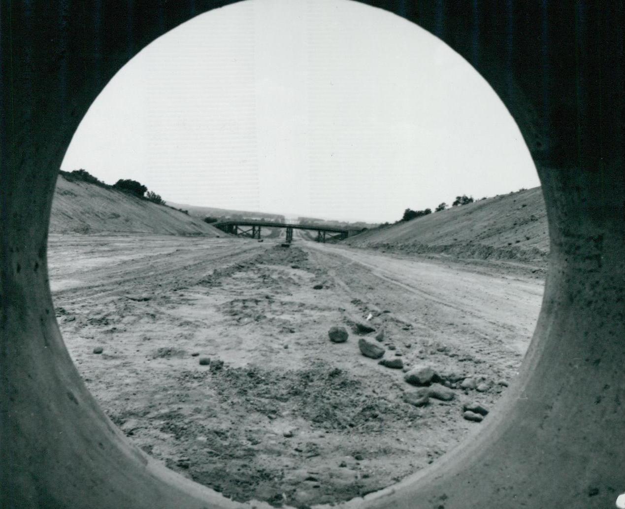 Az M3-as autópálya épülő felüljárója, vasbeton közműcső mögül fotózva