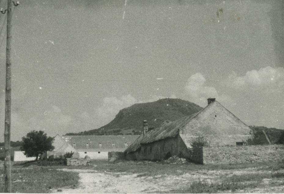 A volt Eszterházy uradalmi gazdasági épület Gyulakeszin, háttérben a Csobánc-heggyel